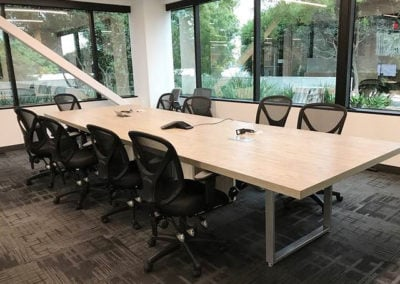 Long conference table with black mesh back chairs