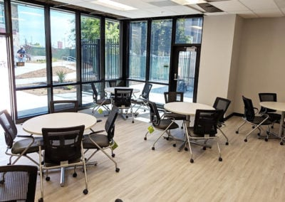 Round cafe tables with mesh back black chairs in break room